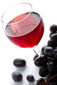 Glass of red wine and grapes isolated — Stock Photo