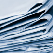 Stack of newspapers toned blue — Stock Photo