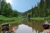 Fishermen float on the river — Stock Photo