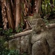 Ancient statue in the forest - Photo