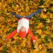 Stock Photo: Cute little girl lying in autumn leaves