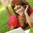 Young woman with laptop outdoors - Stock Photo
