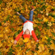 Cute little girl lying in autumn leaves — Stock Photo