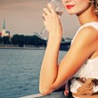 Beautiful woman drinks chamlagne near the river — Stock Photo #1421442