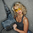 Royalty-Free Stock Photo: Beautiful blond woman with heavy drill in her ha
