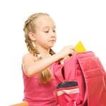 Little schoolgirl packing her rucksack — Stock Photo