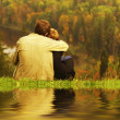 Stockfoto: Sweet couple sitting on hill and looking at th