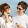 Stock Photo: Happy young couple listening to music