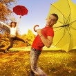 Foto Stock: Funny couple with umbrellas on autumn background