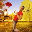 Funny couple with umbrellas on autumn background — Стоковая фотография