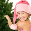 Little santa girl near christmas tree — Stock fotografie