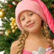 Santa girl near the christmas tree — Stock fotografie