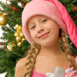 Santa girl near the christmas tree - Stock Photo