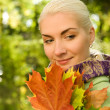 Woman with golden autumn leaves — Stock Photo #1422672