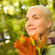 Woman with golden autumn leaves — Stock Photo