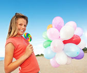 Happy girl with balloons and sweet candy — Stock Photo
