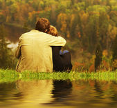 Sweet couple sitting on a hill and looking at th — Foto Stock