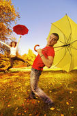 Funny couple with umbrellas on autumn background — Foto Stock