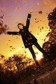 Młoda dziewczyna rzuca jesienią liście — Zdjęcie stockowe