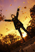 年轻女孩投掷秋天叶子 — 图库照片