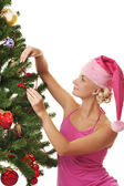 Santa girl decorating the christmas tree — Stock Photo