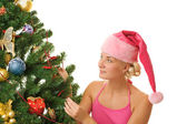 Santa girl decorating christmas tree — Stock Photo