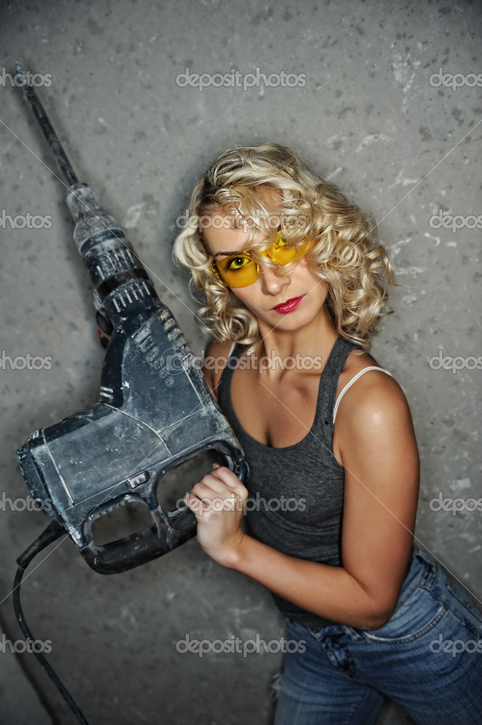 Beautiful blond woman with heavy drill in her hands  Stock Photo #1421552