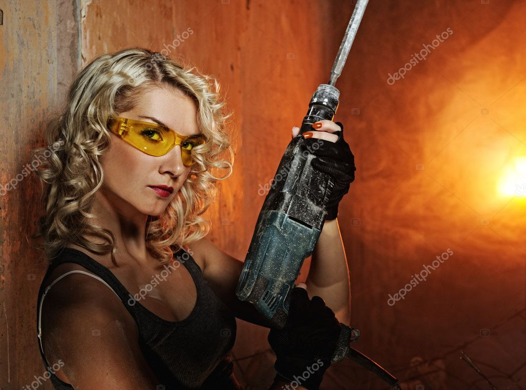 Beautiful blond woman with heavy perforator in her hands — Stock Photo #1421569