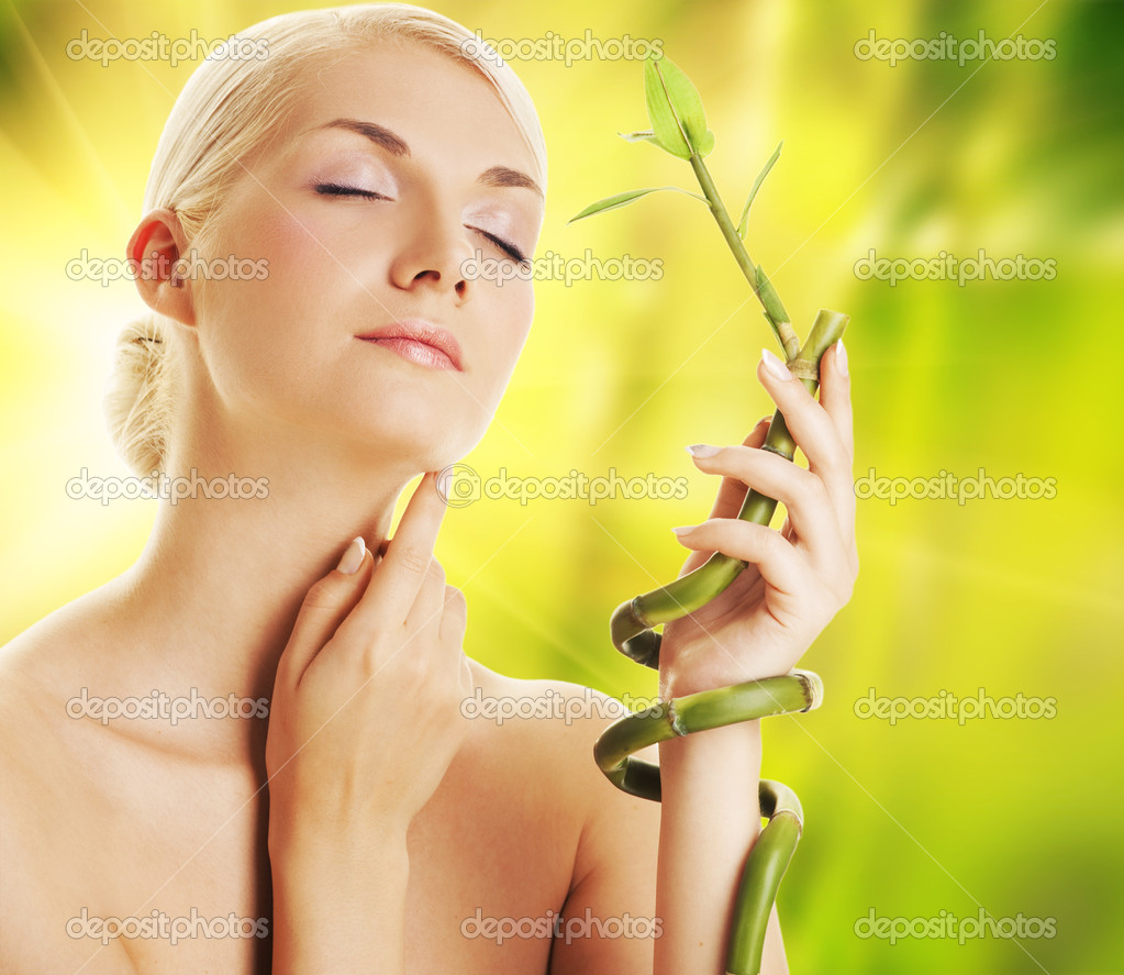  Beautiful young woman with a bamboo plant  Stock Photo #1422495