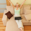Young woman sitting on sofa with laptop — Stock Photo #1728095