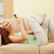 Woman lying on a sofa and writing sms — Stock Photo