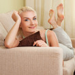 Young happy woman lying on a sofa — Stock Photo #1728869