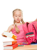 Little schoolgirl packing her rucksack — Stock Photo