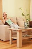Donna seduta sul divano — Foto Stock