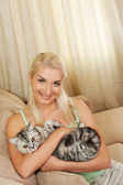 Young woman with cat stitting on sofa — Stock Photo