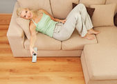 Woman lying on a sofa with TV remote — Stock Photo