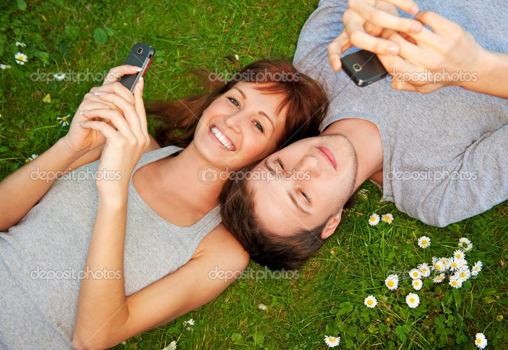 Young couple with mobile phones outdoors  Foto de Stock   #1728143