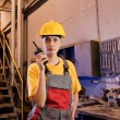 Factory worker talking on the phone - Stock Photo
