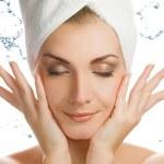 Beautiful young woman washing her face — Stock Photo