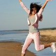 Young woman jumping on the beach — Stock Photo #1741684