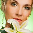 Beautiful young woman with lily flower — Stock Photo