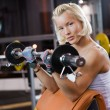 Strong beautiful woman lifting heavy weights — Stock Photo #1746727