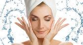 Mujer joven hermosa que se lava la cara — Foto de Stock