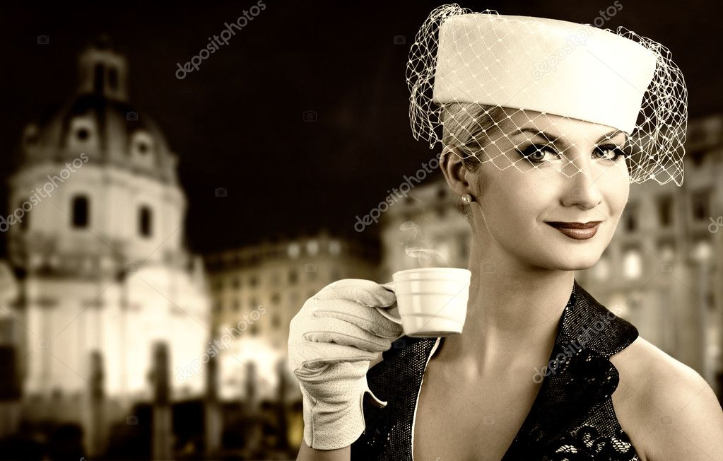 Beautiful young woman drinking coffee. Old city background behind her — Stock Photo #1741554