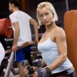 Strong beautiful woman lifting heavy dumbbells — Stock Photo