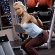 Strong beautiful woman lifting heavy weights — Stock Photo