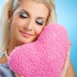 Young woman with fluffy heart pillow — Stock Photo