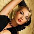 Lovely woman on golden fabric - Stock Photo