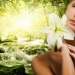 Beautiful woman with flower in forest — Stock Photo
