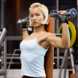 Strong woman lifting heavy dumbbells — Stock Photo #2084972